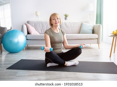 Positive mature woman in sports clothes doing strength exercises with dumbbells at home, free space. Happy senior lady working out with weights on yoga mat during covid-19 isolation