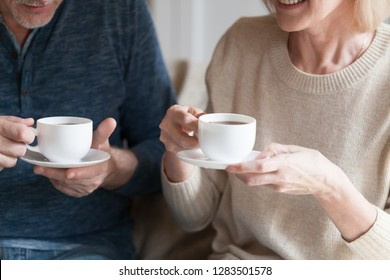 Positive middle aged spouses sitting at home holding cups with black tea beverage. Mature senior wife and husband spending time together drinking afternoon coffee and chatting, close up cropped image