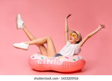 Positive millennial blonde sitting on big inflatable ring, ready to swim, pink studio background