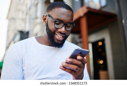 Positive millennial man chatting online on smartphone spending time outdoors in urban setting, cheerful hipster blogger reading notification on mobile phone connected to free public wifi internet