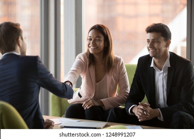 Positive millennial middle eastern ethnicity businessman and african american businesswoman greeting company client, customer rear view, sitting on couches shaking hands ready to start conversation