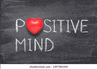 positive mind phrase written on chalkboard with red heart symbol