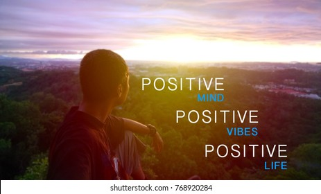 positive mind, positive vibes, positive life quote with single man sit on high peak rock during sunset. selected focus and warm tone