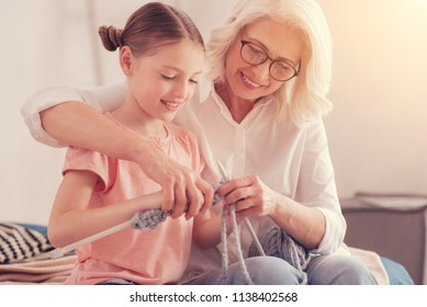 Positive minded retired lady sitting next to her cute grandchild while helping her with knitting during a leisure time spent at home.