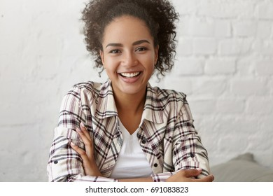 Positive mixed race female with curly dark hair and gentle smile, sitting against white wall indoors, keeping her hands crossed feeling relaxation. African girl with joyful expression posing at camera
