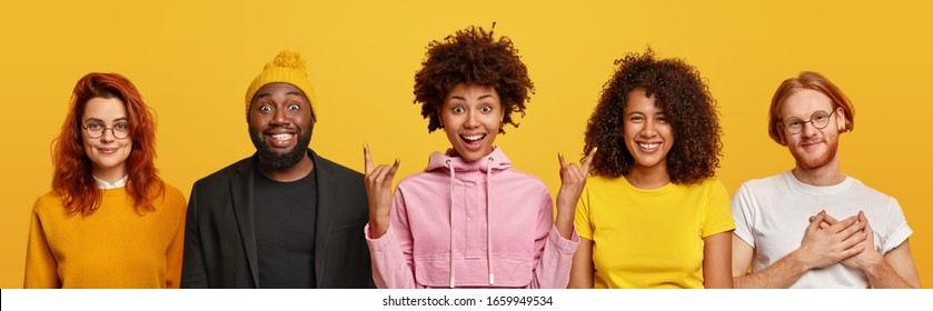 Positive mixed race friends pose together, stand next to each other. African American woman shows rock n roll gesture, ginger man keeps hands on heart, expresses gratitude, smile positively.