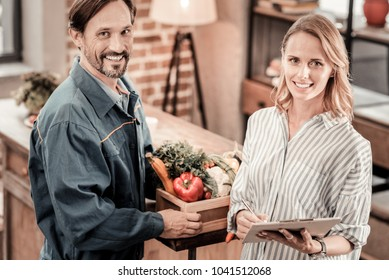 Positive mood. Joyful nice attractive woman holding a delivering paper and signing it while looking at you