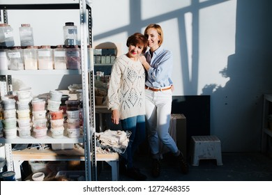 Positive mother and daughter posing in a workshop pantry on a bright day. Standing next to big shelf full with paints.