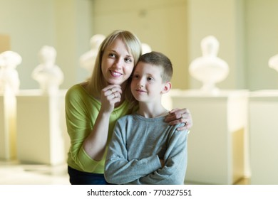 Positive mother and son regarding ancient statues in museum