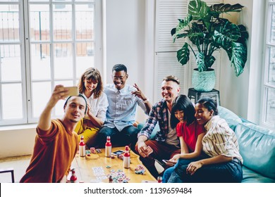 Positive multicultural friends dressed in casual wear making selfie photos on front camera of modern smartphone for publication in blog ad spending time together playing poker in apartment