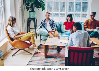 Positive multicultural young people dressed in casual apparel spending free time together playing game in modern flat with stylish interior.Cheerful hipsters communicating with each other