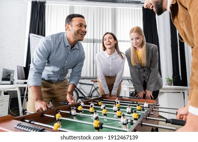Positive multiethnic business people standing near table soccer in office