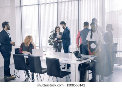 Positive multiracial diverse business people in formal and casual wear are discussing forum topics and sharing impressions while standing in conference room at break. Toned image