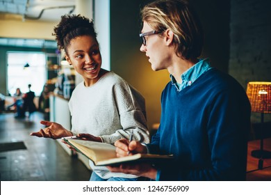 Positive multiracial male and female students having conversation about common project in cafe making notes, man writing to do list in notepad while talking and discussing with his girlfriend