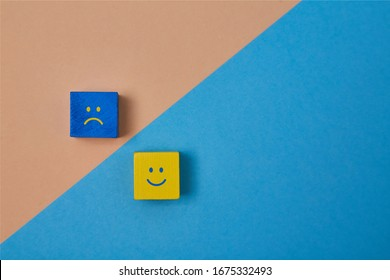 Positive and negative emotions. Positivity and negativity of thinking. Smiling and sad emoji on colorful wooden cubes