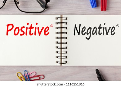 Positive or negative written on notebook on wooden desk with marker pen and glasses.