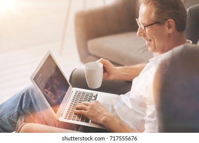 Positive nice man looking at the laptop screen
