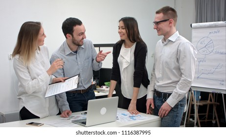 Positive office people laughing at a joke told by male coworker