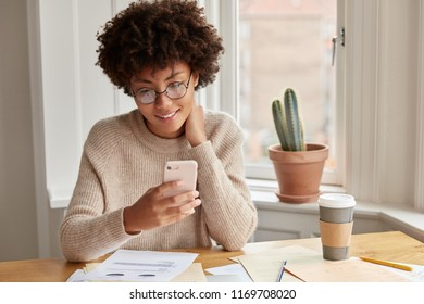 Positive owner of trading corporation holds modern smart phone, checks email box, waits for message from marketing expert, surrounded with documentation, surfes popular website, searches internet