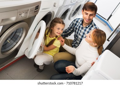 Positive parents with daughter choosing washing machine in home appliance store. Focus on girl