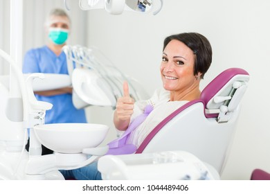 positive patient female thumbs up about work of dantist in medical room