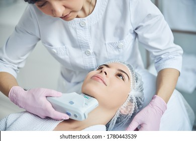 Positive patient undergoing non invasive chin treatment using ultrasound lifting tool