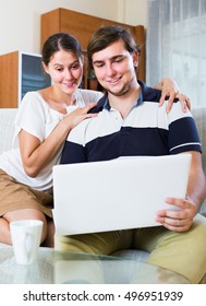 Positive  people sitting on couch and surfing internet