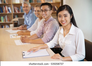 Positive people smiling at camera in library