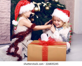 positive photo of cute beautiful little girls in Santa's hat playing beside a decorated Christmas tree and presents