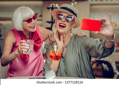 Positive photos. Delighted positive woman holding her smartphone while taking a selfie together with her friend