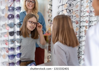 Positive pleasant girl looking in the mirror while wearing new glasses