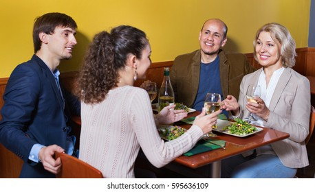 Positive pleasant middle class people enjoying food and wine in cafe