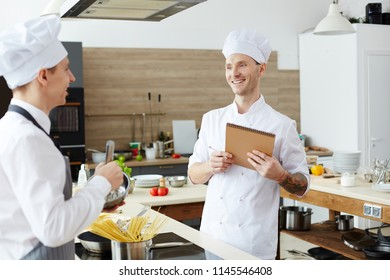 Positive pleased handsome young chef with tattoo on arm making notes in sketchpad while testing intern cook at class