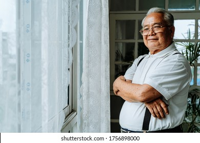 Positive plump senior Asian male smiling for camera and crossing arms while resting near window in cozy room at home