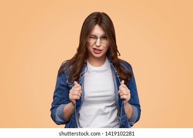Positive plus size female adjusting denim jacket and winking for camera while standing against beige background