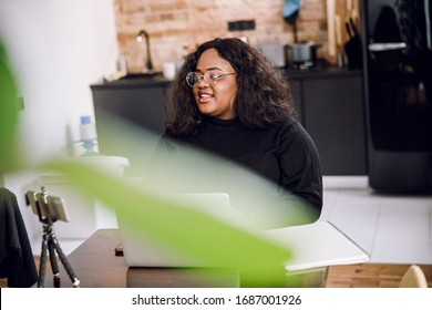 Positive plus size woman in the kitchen sitting in front of her gadgets and smiling