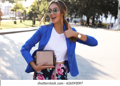 Positive portrait of happy woman making selfie,sure funny faces,grimaces,joy,emotions,casual style,pastel colors,spring summer concept.hold purse bag,Sending air kiss, and say ok.fashion sunglasses