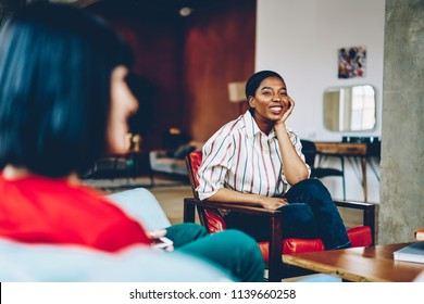 Positive pretty african american young woman attentively listening friends during discussion of games rules.Stylish dressed dark skinned hipster girl sitting on cozy chair and spending time in flat