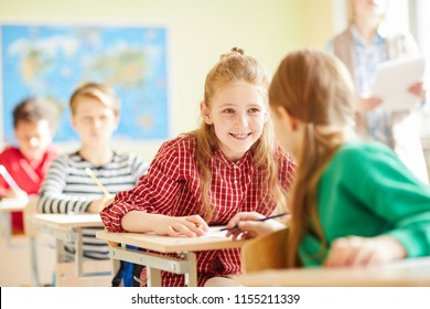 Positive pretty classmates in casual clothing sitting at desks and talking to each other at lesson
