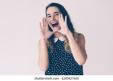 Positive pretty woman cupping hands around mouth and shouting loud. Announcement concept. Isolated front view on white background.