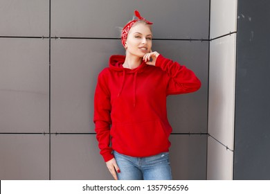 Positive pretty young woman in trendy red hooded sweatshirt with a stylish bandana in jeans is standing and smiling in the city near a gray building. Happy girl enjoys a walk. American modern style.