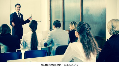 Positive professor and serious professionals at extension business courses indoors. Focus on blonde girl