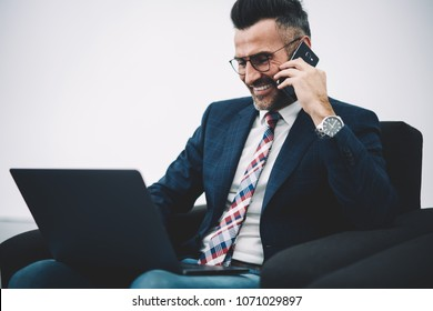 Positive prosperous businessman in suit laughing during phone call on smartphone while making money payment online on laptop via wireless 4G internet in office.Mature proud ceo working at netbook