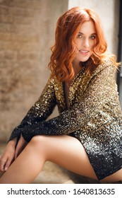 Positive red-haired smiling beautiful girl dressed in a black-gold jacket sits on a window sill against the background of a brick wall. Fashion shooting hairstyles and make-up.