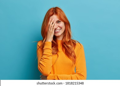 Positive redhead European woman makes face palm and feels shy hears hilarious joke and giggles positively dressed in casual orange jumper isolated on blue background. Happy emotions or feelings
