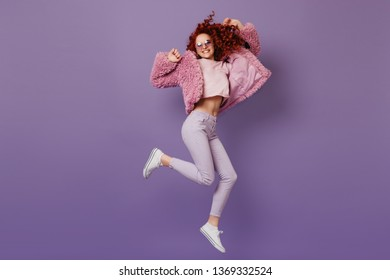 Positive redhead girl in eco-coat, pink top and white pants jumping on lilac background