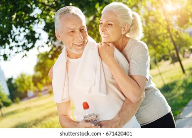 Positive retired smiling couple resting in the park after jogging