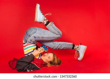 Positive retro styled fashionable woman in sport jacket and jeans with vintage cassette player on red background. Fashion back to 80s - 90s new trend concept