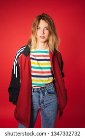 Positive retro styled fashionable woman portrait in sport jacket and jeans on red background. Fashion back to 80s - 90s new trend concept