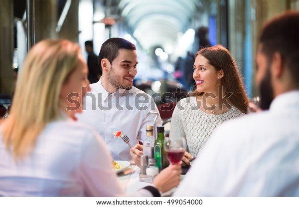 Positive russian middle class people enjoying food in cafe terrace